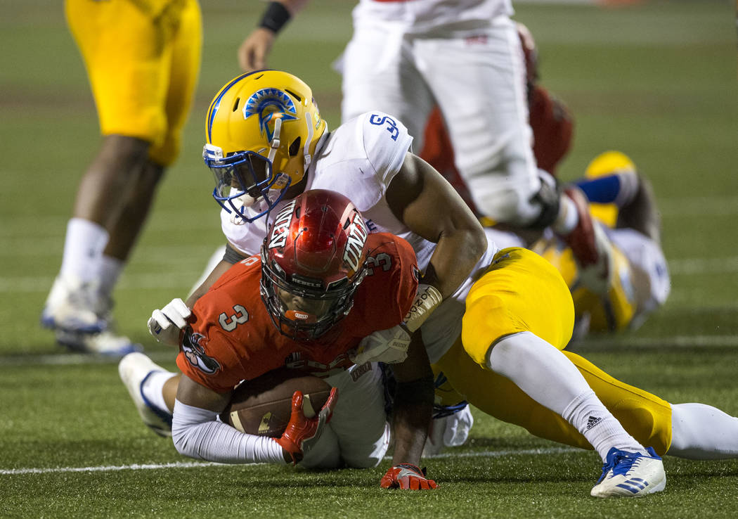 UNLV Rebels running back Lexington Thomas (3) is brought down by San Jose State Spartans defenders during the second half of an NCAA college football game between the UNLV Rebels and the San Jose  ...