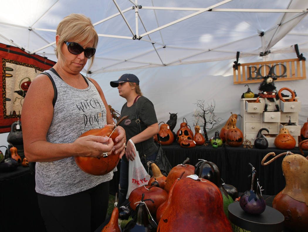 Las Vegas local Stacey Seidl looks at hand-carved pumpkins from Out of Our Gourds during the Art in the Park festival in Boulder City, Saturday, Oct. 7, 2017. Gabriella Benavidez Las Vegas Review- ...