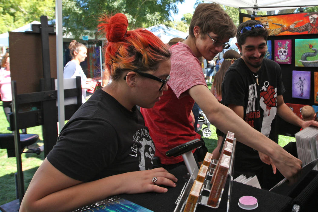 From left, Ana-Michele Johnson, 16, Alexander Metzger, 18 and Michael Donohue, 18, look at smaller prints of artist David Lozeau's work during the Art in the Park festival in Boulder City, Saturda ...