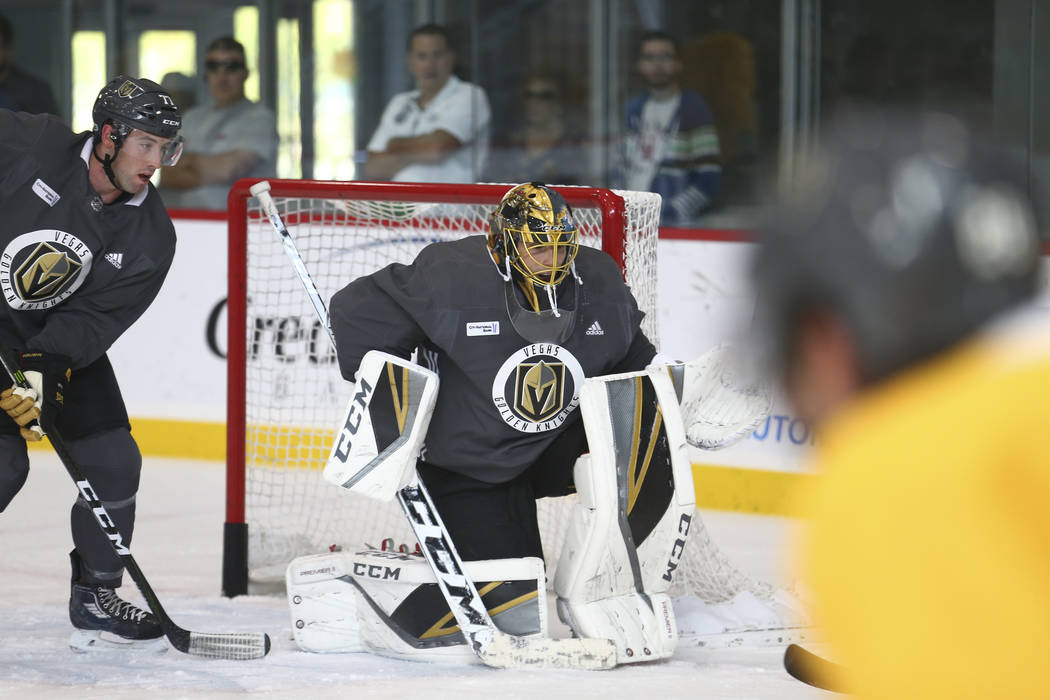 Vegas Golden Knights defenseman Brad Hunt (77) and Knights goalie Marc-Andre Fleury (29) watch the puck in a drill during the NHL team's practice at the City National Arena in Las Vegas, Wednesday ...