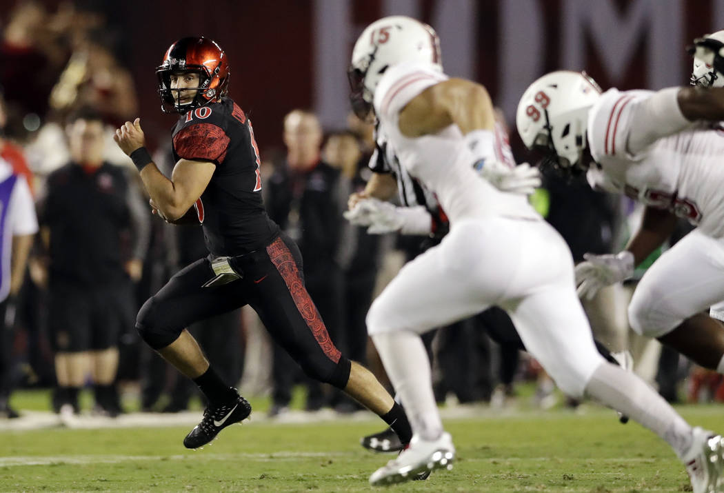 San Diego State quarterback Christian Chapman, left, runs with the ball during the first half of an NCAA college football game against Northern Illinois Saturday, Sept. 30, 2017, in San Diego. (AP ...