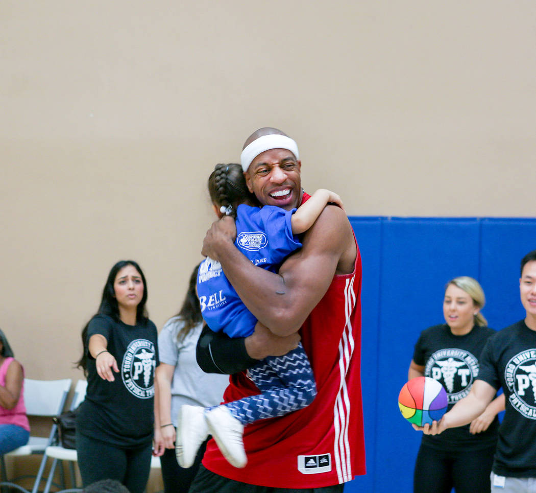 "Former NBA player Jerome ""Junkyard Dog"" Williams hugs a child after he helped them make basket during the Center for Autism and Developmental Disabilities Basketball Clinic at To ..."