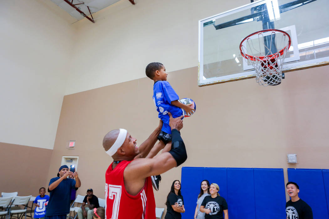 "Former NBA player Jerome ""Junkyard Dog"" Williams holds  Zollin Ellis, 5, to make a basket during the Center for Autism and Developmental Disabilities Basketball Clinic at Touro U ..."