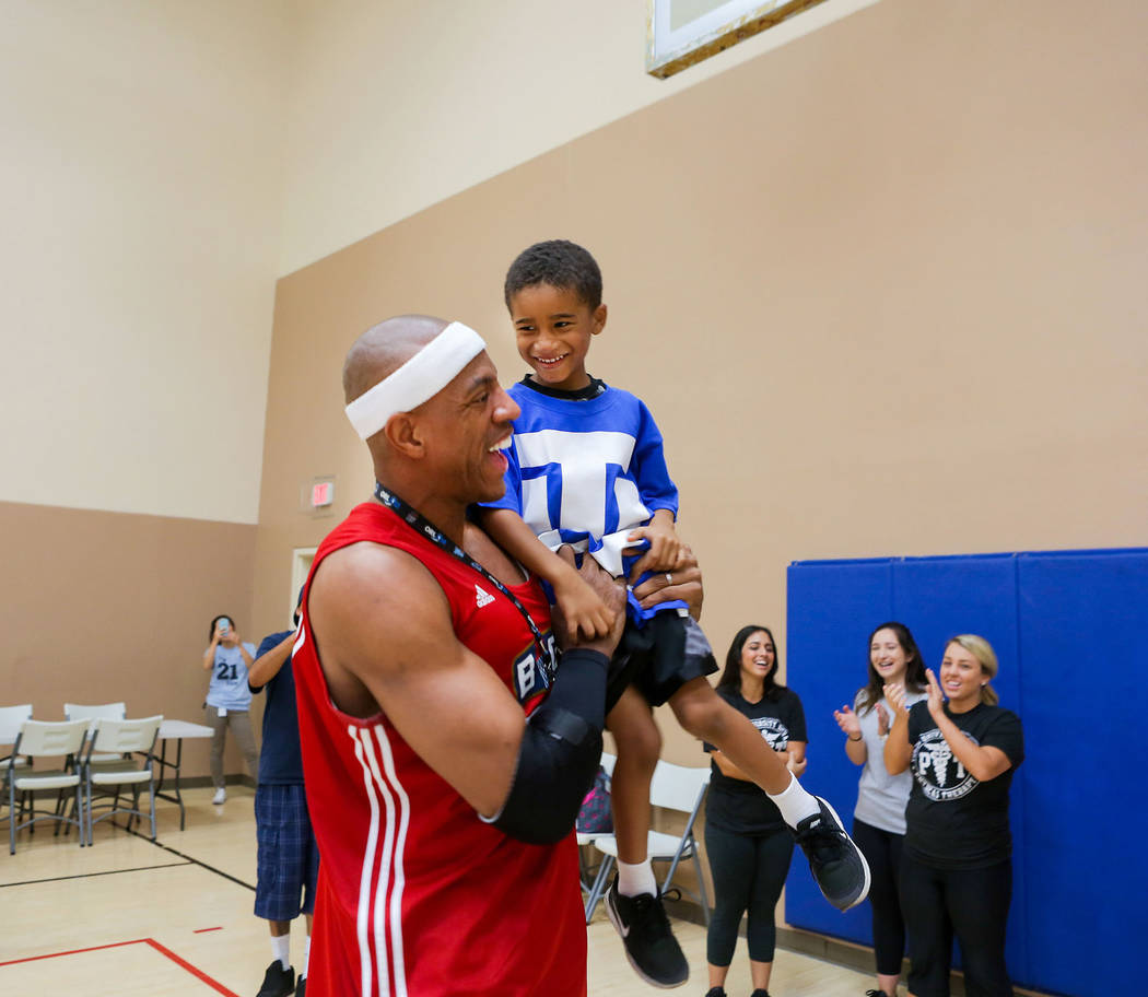 "Former NBA player Jerome ""Junkyard Dog"" Williams holds  Zollin Ellis, 5, after making a basket during the Center for Autism and Developmental Disabilities Basketball Clinic at Touro University in  ..."