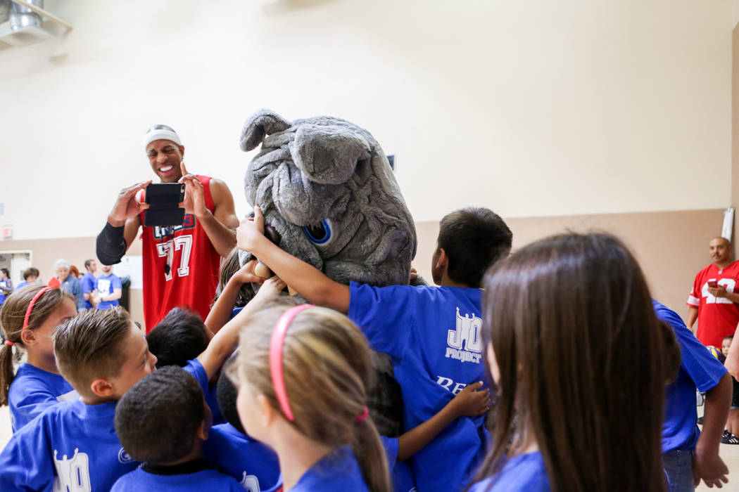 "Former NBA player Jerome ""Junkyard Dog"" Williams, left, takes a video of kids hugging his mascot during the Center for Autism and Developmental Disabilities Basketball Clinic at  ..."