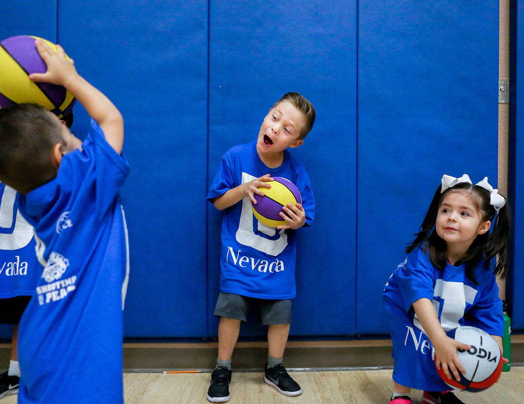 Sebastian Sanchez, 3, left, Mateo Sanchez, 6, and Carolina Sanchez, 3, practice dribbling during the Center for Autism and Developmental Disabilities Basketball Clinic at Touro University in Hende ...
