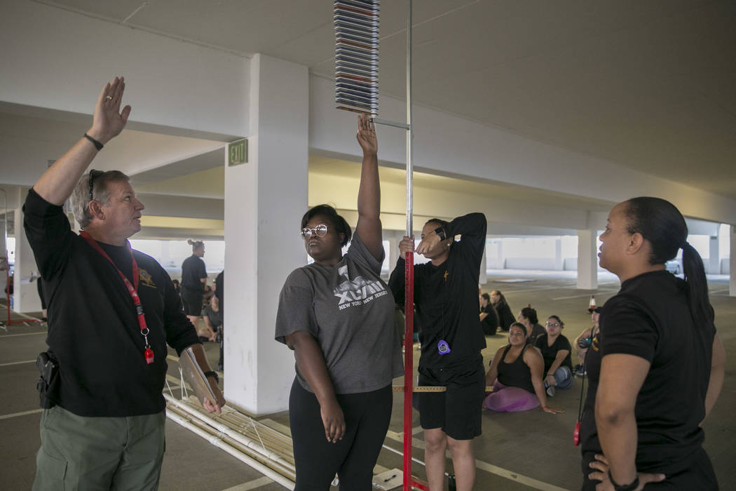 Alexis Walker of North Las Vegas, center, receives feedback from officer Daryl Keithley on her vertical jump during Las Vegas Metropolitan Police Department's women's boot camp in the parking gara ...