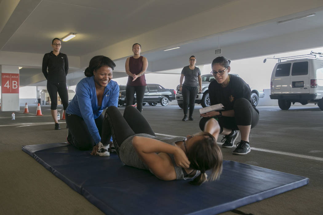 Delia Sherroll, left, helps Judith Gomez, center, do timed crunches during Las Vegas Metropolitan Police Department's women's boot camp in the parking garage of the Las Vegas Metropolitan Police D ...