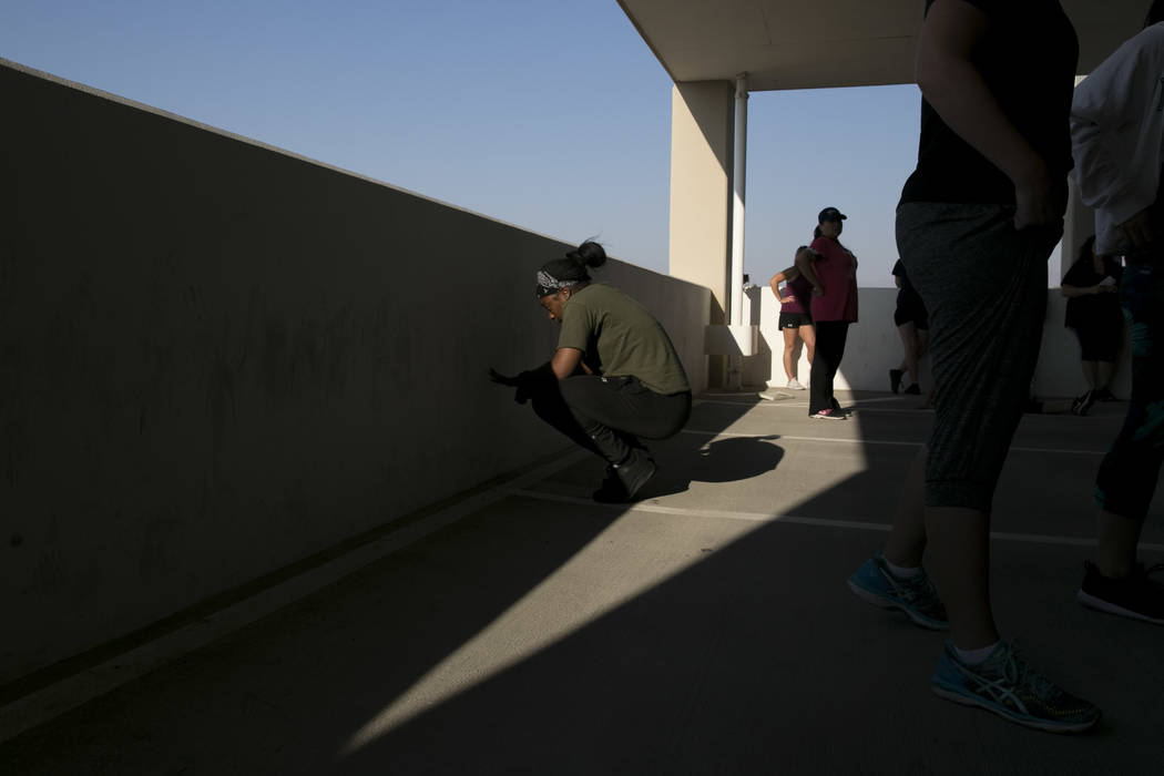 Jaquoia Hanson rests after running a timed 300 meter run during Las Vegas Metropolitan Police Department's women's boot camp in the parking garage of the Las Vegas Metropolitan Police Department i ...