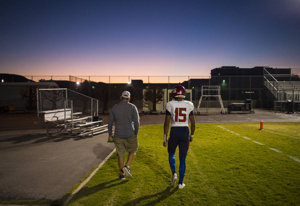 Coronado head coach William Froman, left, walks with Coronado's Ayzayah Hartfield (15), son of fallen Las Vegas police officer Charleston Hartfield, before a football game at Basic High School in  ...