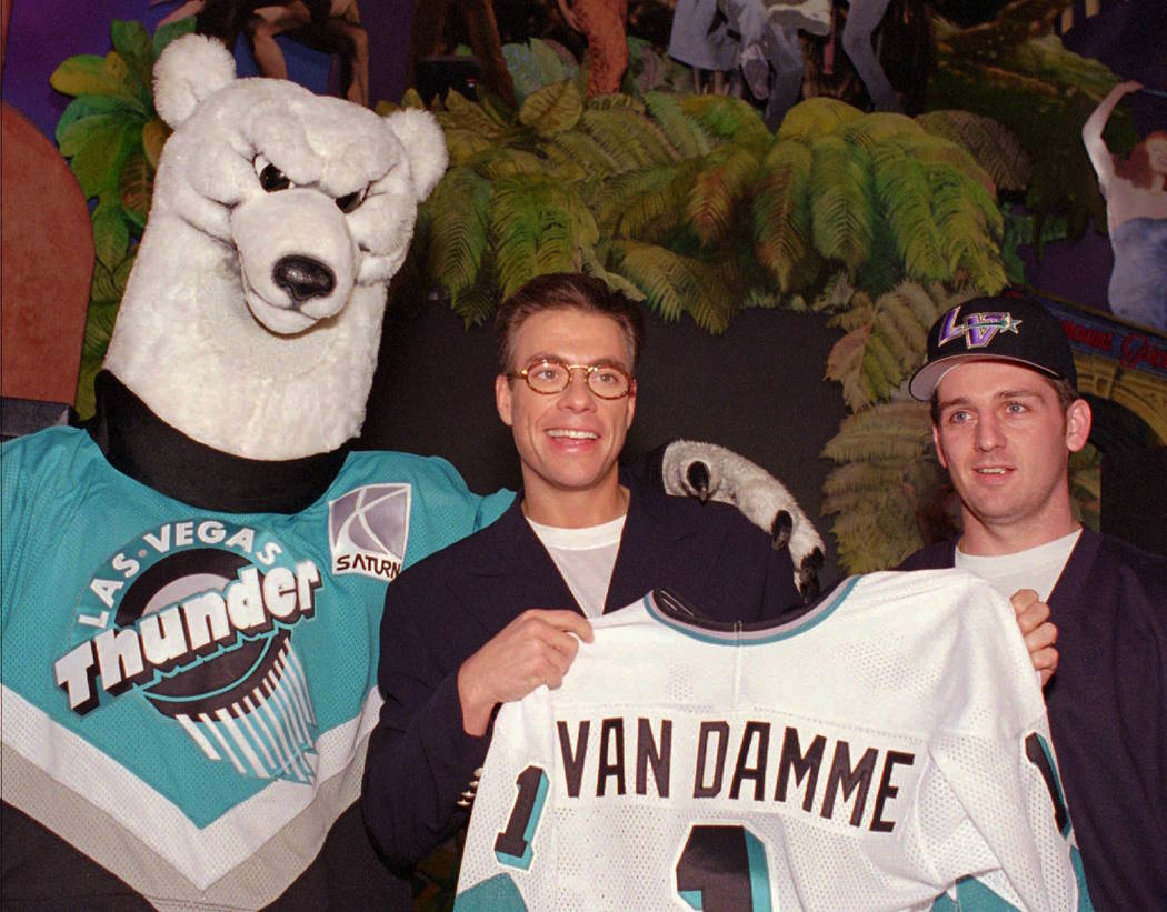 """Actor Jean-Claude Van Damme, center, is presented an honorary Las Vegas Thunder jersey by Greg Hawgood, right, captain of the minor-league hockey team, and team mascot """"Boom Boom"""" during a stop at ..."""