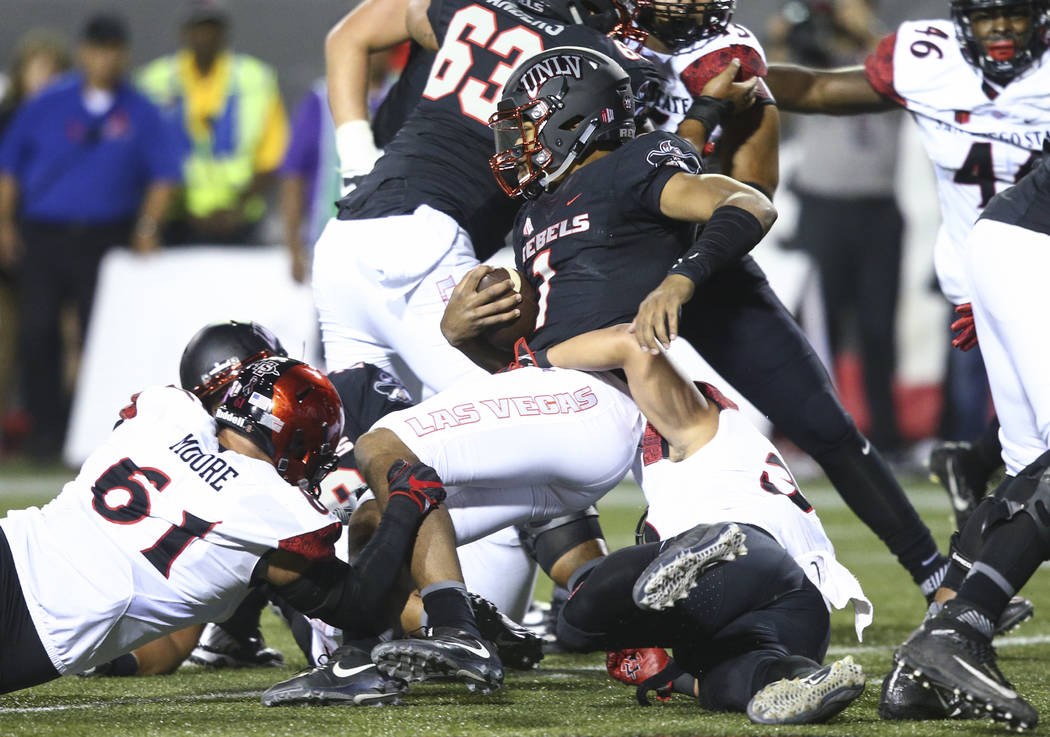 UNLV's Armani Rogers (1) is taken down by San Diego State's Damon Moore, left, and Ronley Lakalaka, right, during a football game at Sam Boyd Stadium in Las Vegas on Saturday, Oct. 7, 2017. Chase  ...
