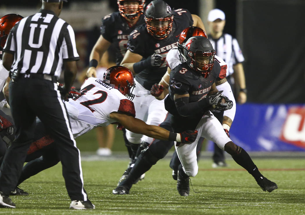 UNLV's Lexington Thomas (3) runs the ball as San Diego State's Troy Cassidy (42) defends during a football game at Sam Boyd Stadium in Las Vegas on Saturday, Oct. 7, 2017. Chase Stevens Las Vegas  ...