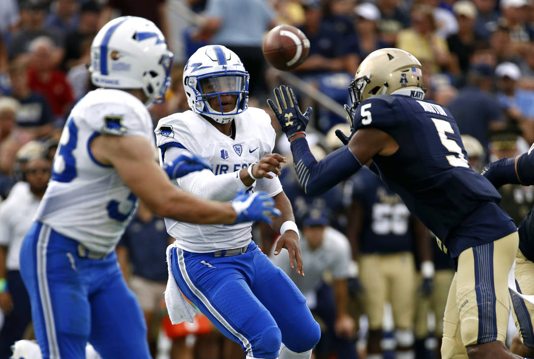Air Force quarterback Arion Worthman, center, throws a pass to running back Timothy McVey, left, as he is pressured by Navy linebacker Justin Norton in the first half of an NCAA college football g ...