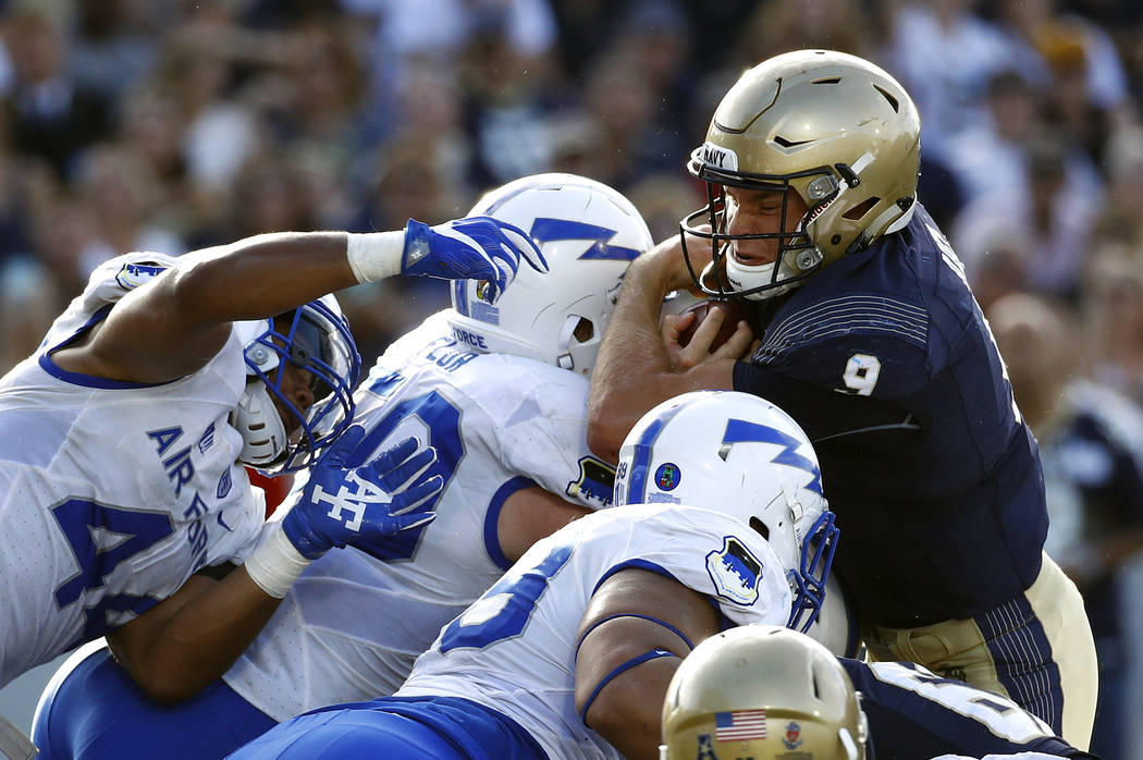 Navy quarterback Zach Abey, right, pushes through Air Force defenders for a touchdown in the first half of an NCAA college football game in Annapolis, Md., Saturday, Oct. 7, 2017. (AP Photo/Patric ...