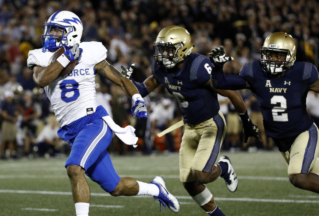Air Force wide receiver Marcus Bennett, let, runs for a touchdown past Navy safeties Sean Williams, center, and Jarid Ryan in the second half of an NCAA college football game in Annapolis, Md., Sa ...