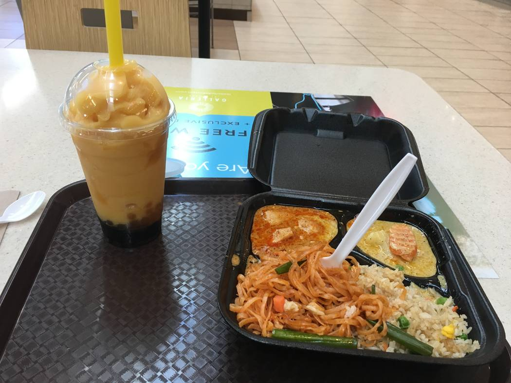 A peach boba drink served with a main entree of pad thai noodles and fried rice alongside the two types of curry Tom Yum serves: yellow and panang. (Diego Mendoza-Moyers/View) @dmendozamoyers