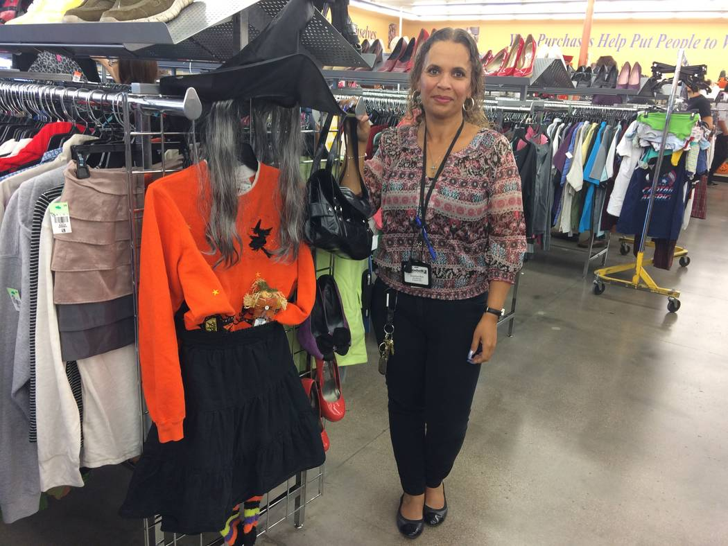 Jackie Reed, store manager at Goodwill on South Fort Apaches, poses by a Halloween end display, pulled together by staffers. A new poll by the National Retail Federation reports that two-thirds of ...
