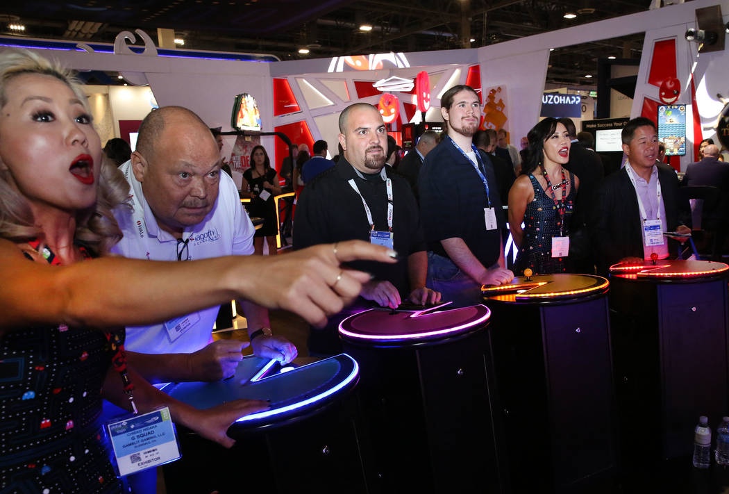 Chieko Hidaka, left, of Gamblit Gaming, reacts as expo goers, including Mike Davis, second left, play Pac-Man Battle at the Gamblit Gaming booth during Global Gaming Expo at the Sands Expo and Con ...