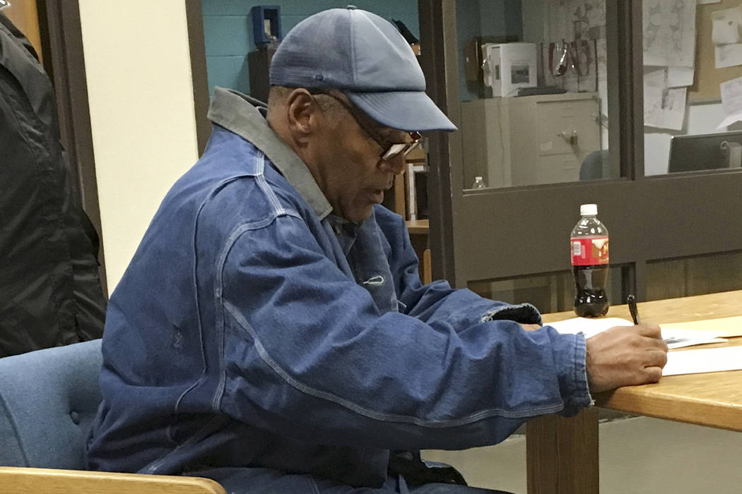 O.J. Simpson signs documents at the Lovelock Correctional Center, Saturday, Sept. 30, 2017, in Lovelock, Nevada. (Brooke Keast/Nevada Department of Corrections via AP)
