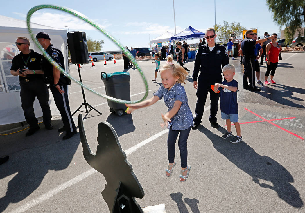 Brooklyn Brosnahan, 5, center, of Las Vegas throws a hoop during a fundraising event for the victims of Hurricanes Harvey and Irma at the Nevada Highway Patrol Southern Command in Las Vegas, Sunda ...