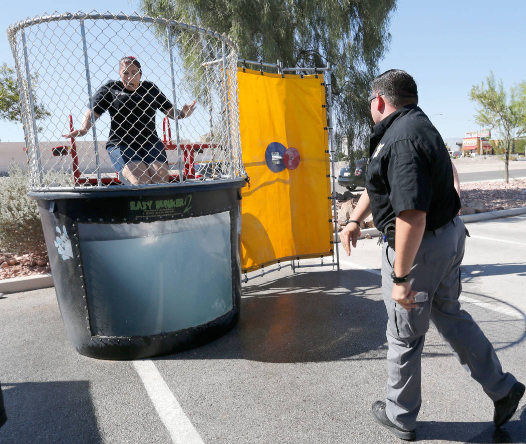 Public Safety Dispatcher Sonia Vasquez goes down to the dunk tank as Department of Public Safety Sgt. Shannon Serena strikes a target during a fundraising event for the victims of Hurricanes Harve ...