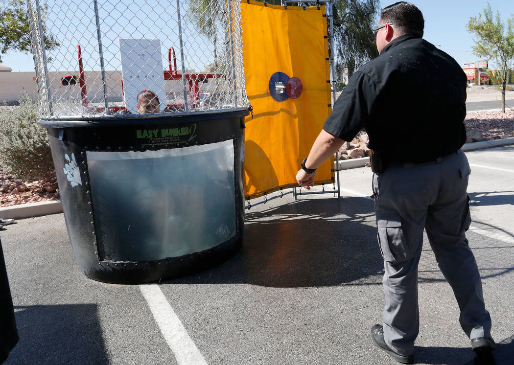 Public Safety Dispatcher Sonia Vasquez goes dawn to the dunk tank as Department of Public Safety Sgt. Shannon Serena strikes a target during a fundraising event for the victims of Hurricanes Harve ...