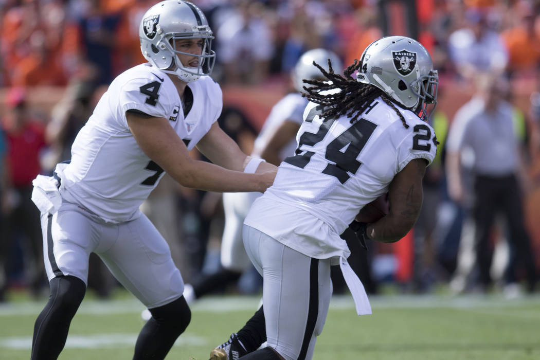Oakland Raiders quarterback Derek Carr (4) hands off the football to running back Marshawn Lynch (24) in the first half of their game against the Denver Broncos in Denver, Colo., Sunday, Oct. 1, 2 ...
