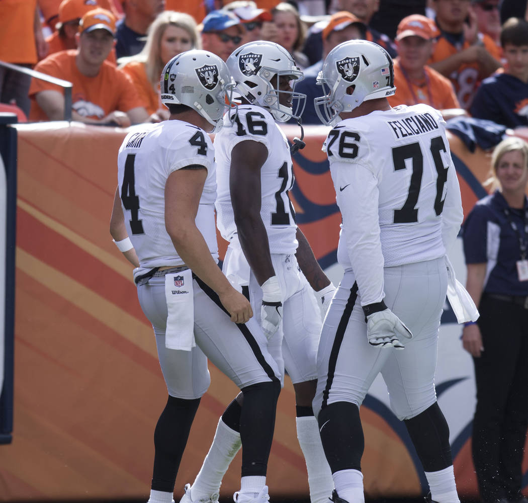 Oakland Raiders wide receiver Johnny Holton (16) celebrates his touchdown with offensive guard Jon Feliciano (76) and quarterback Derek Carr (4) in the first half of their game against the Denver  ...