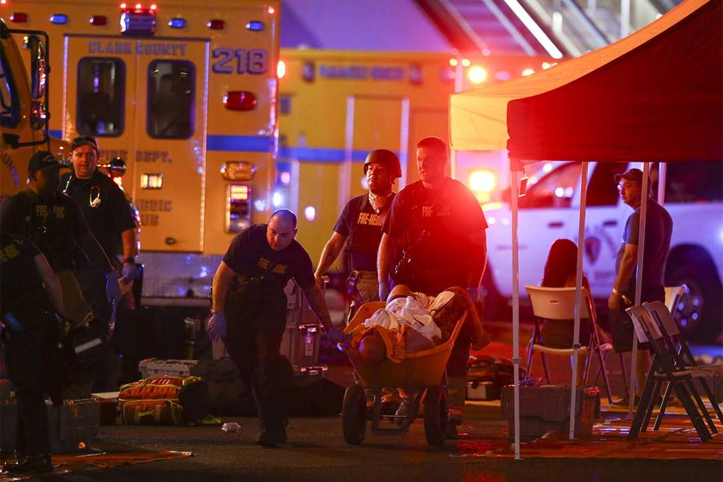 A wounded person is walked on a wheelbarrow as Las Vegas police respond during an active shooter situation on the Las Vegas Strip in Las Vegas on Sunday, Oct. 1, 2017. (Chase Stevens/Las Vegas Rev ...