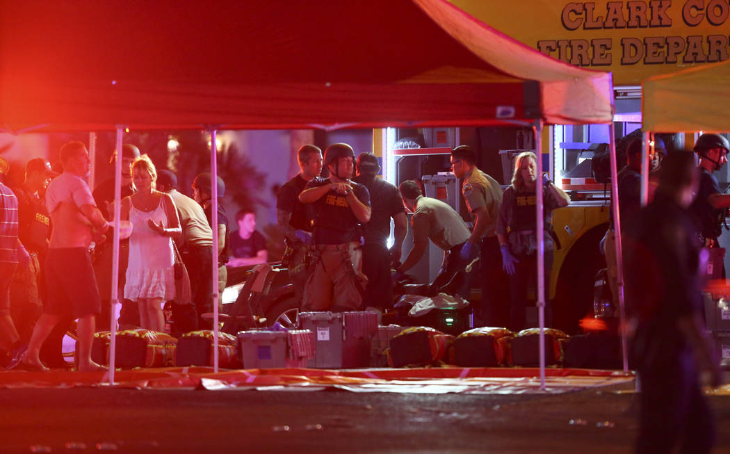 Medics treat the wounded as Las Vegas police respond during an active shooter situation on the Las Vegas Stirp in Las Vegas on Sunday, Oct. 1, 2017. Chase Stevens Las Vegas Review-Journal @cssteve ...