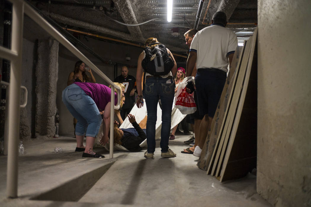 People assist a wounded woman at the Tropicana during an active shooter situation on the Las Vegas Stirp in Las Vegas on Sunday, Oct. 1, 2017. Chase Stevens Las Vegas Review-Journal @csstevensphoto