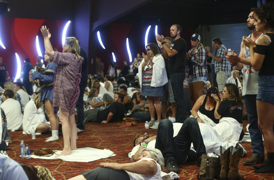 People clap after being updated by a Las Vegas police officer during lockdown at the Tropicana Las Vegas following an active shooter situation that left 50 dead and over 200 injured on the Las Veg ...