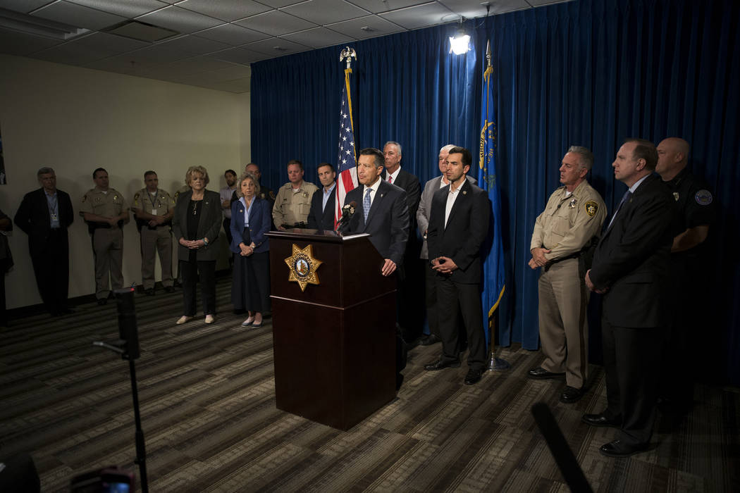 Gov. Brian Sandoval, center, with other state dignitaries, discusses the mass shooting during a press conference at the Las Vegas Metropolitan Police Department headquarters in Las Vegas, Monday,  ...