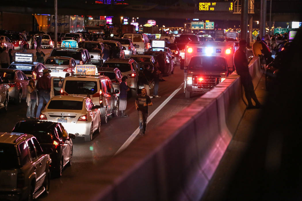 An officer leads an emergency vehicle through stopped traffic on Interstate 15 in Las Vegas after a shooting on the Strip left 58 dead Sunday, Oct. 1, 2017. Joel Angel Juarez Las Vegas Review-Jour ...