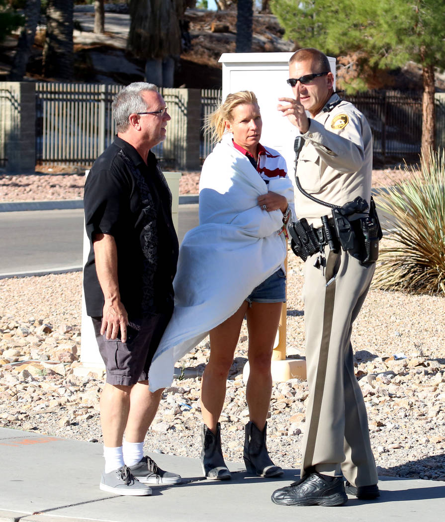 Kathy Boggio-Mocnik and her husband Gary, both of Aliso Viejo, Calif., talk to a Metro police officer as they return to Mandalay Bay hotel-casino on Monday, Oct. 2, 2017 where at least 58 people w ...