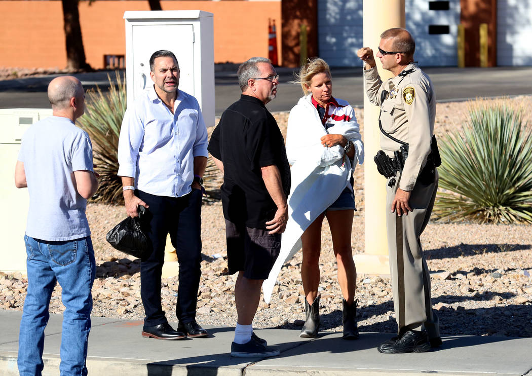 Hotel guests, including Kathy Boggio-Mocnik and her husband Gary, second left, both of Aliso Viejo, Calif., talk to a Metro police officer as they return to Mandalay Bay hotel-casino on Monday, Oc ...