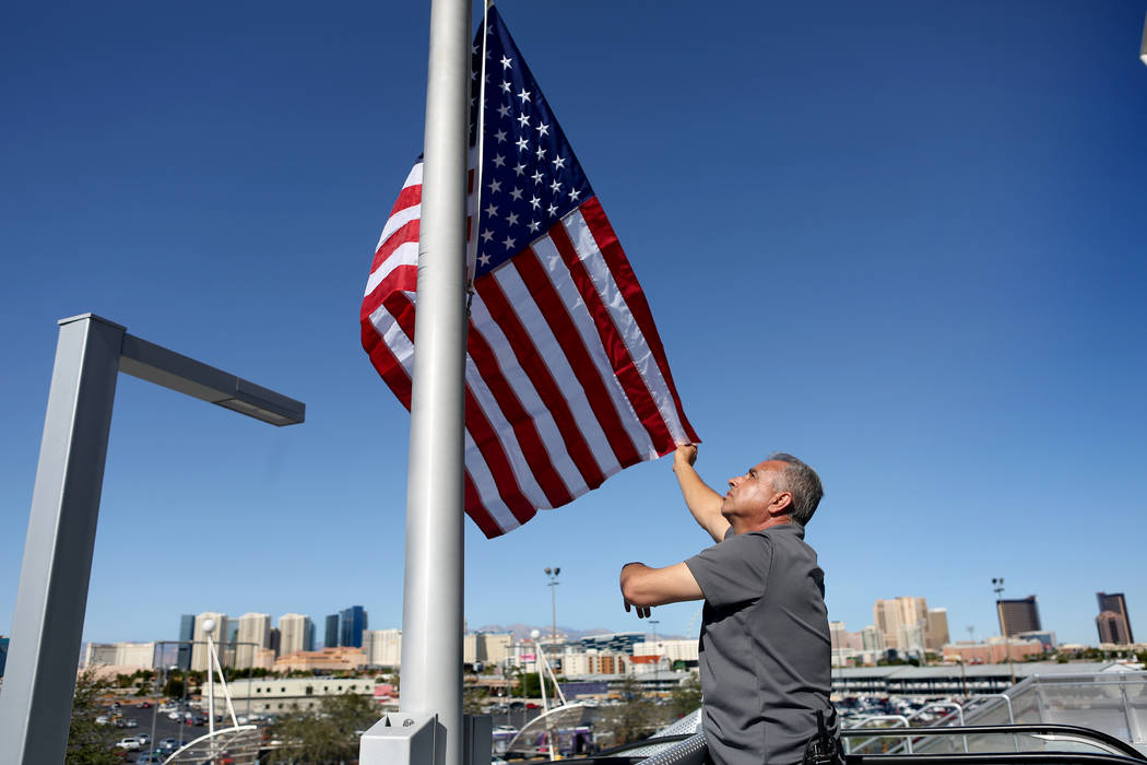 Moises Flores with UNLV facility operations raises a new American flag to half-staff at Thomas & Mack Center in Las Vegas, Monday, Oct. 2, 2017, after a gunman opened fire on the Strip Sunday  ...