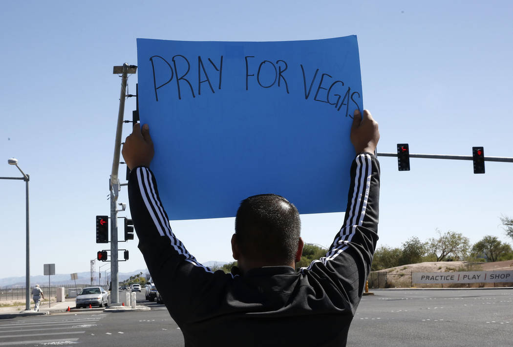 "Jon Dimaya, nurse at Sunrise Hospital, holds a sign that reads ""Pray for Vegas'' on Las Vegas Boulevard near Mandalay Bay hotel-casino on Monday, Oct. 2, 2017. At least 58 people were kil ..."