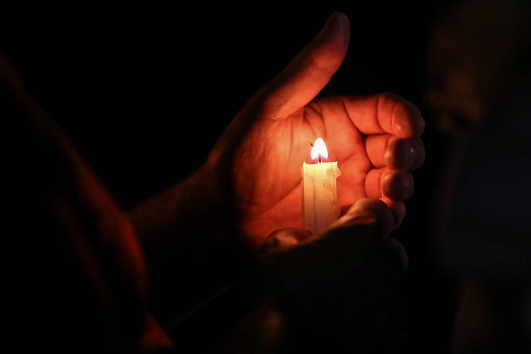 Alberto Henriques, 56, of Las Vegas holds a candle during a vigil near the Town Square Las Vegas in remembrance of the Mandalay Bay shooting victims in Las Vegas, Monday, Oct. 2, 2017. The shootin ...