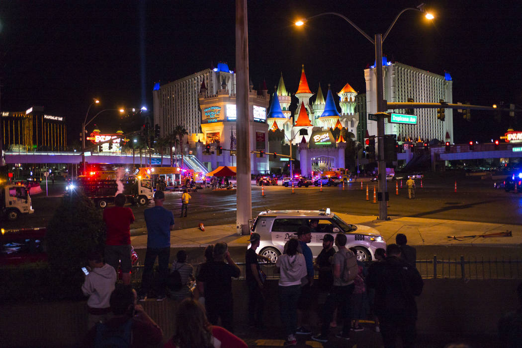Pedestrians look on as Las Vegas police respond during an active shooter situation on the Las Vegas Strip near Tropicana Avenue in Las Vegas on Sunday, Oct. 1, 2017. Chase Stevens Las Vegas Review ...