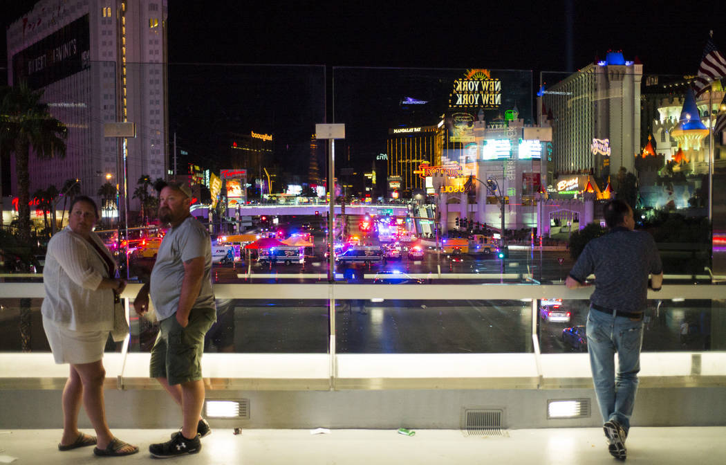 People watch from a pedestrian bridge as Las Vegas police respond during an active shooter situation on the Las Vegas Strip near Tropicana Avenue in Las Vegas on Sunday, Oct. 1, 2017. Chase Steven ...