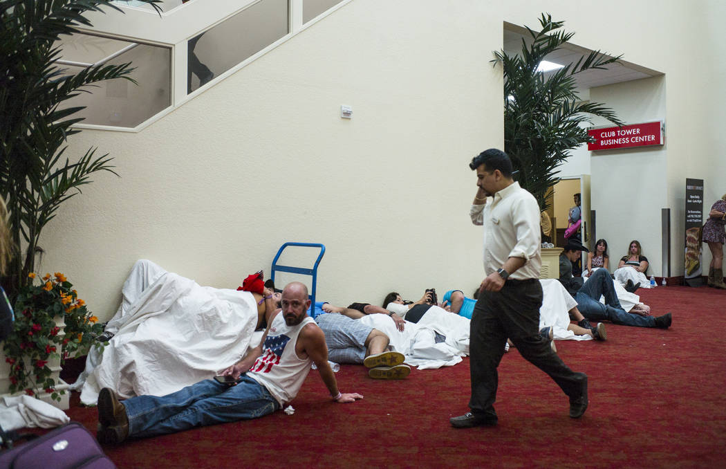 People relax in a convention center area during lockdown at the Tropicana Las Vegas following an active shooter situation that left more than 50 dead and 400 injured on the Las Vegas Strip during  ...