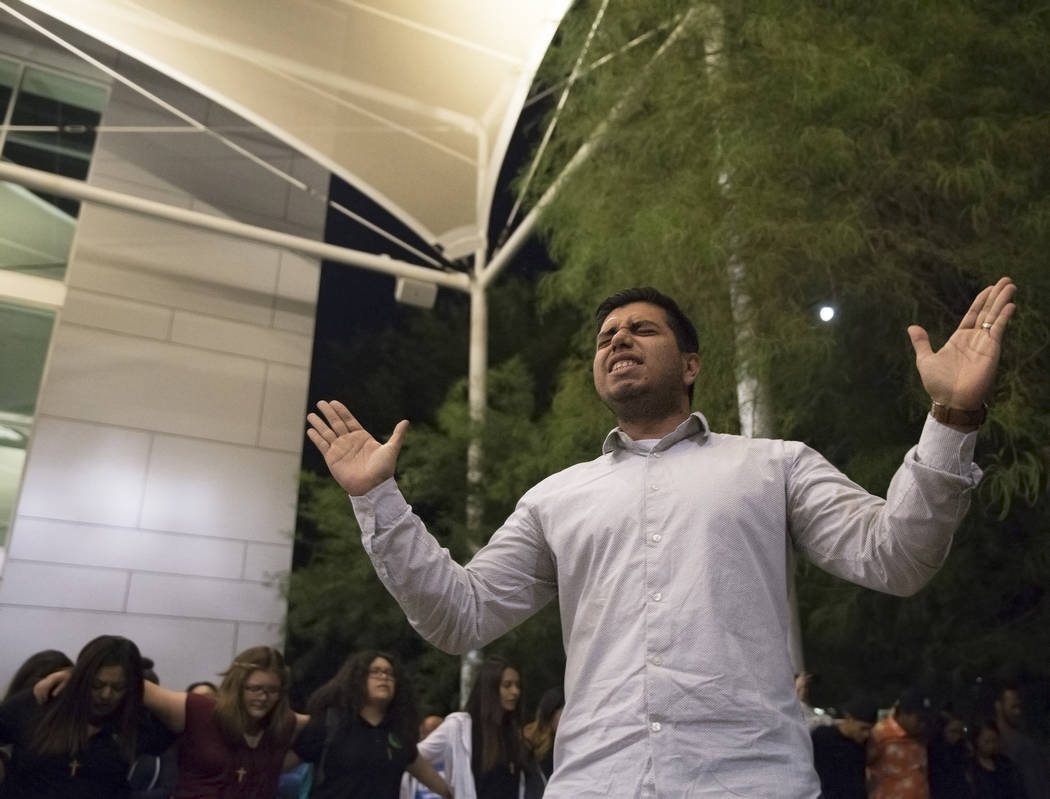 Diego Saravia leads a prayer session during a vigil for the shooting victims of the Route 91 country music festival on Monday, October 2, 2017, at the Student Union courtyard, at UNLV, in Las Vega ...