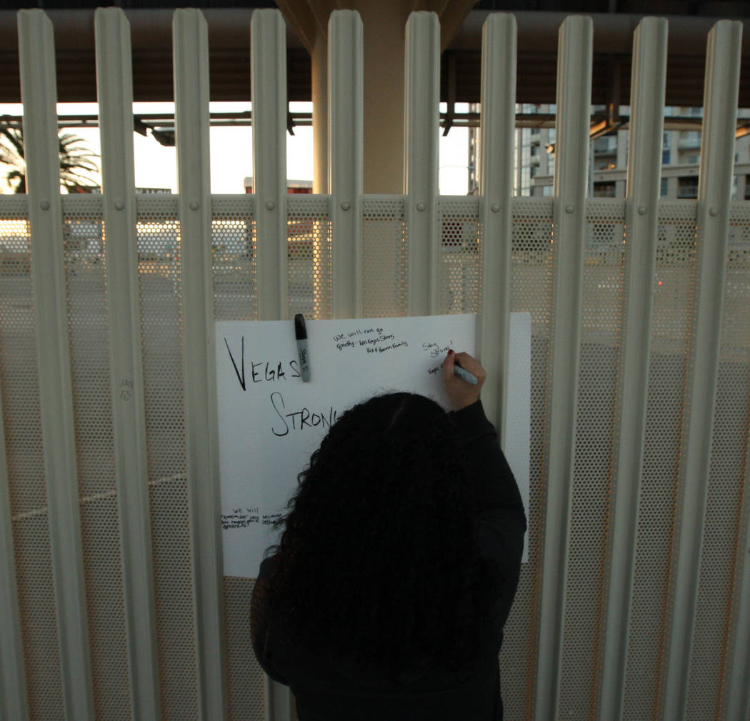 Noelani Epps signs a poster with words of encouragement before a candlelight vigil ceremony near East Sahara Avenue and South Las Vegas Boulevard that honors the victims of the shooting that occur ...