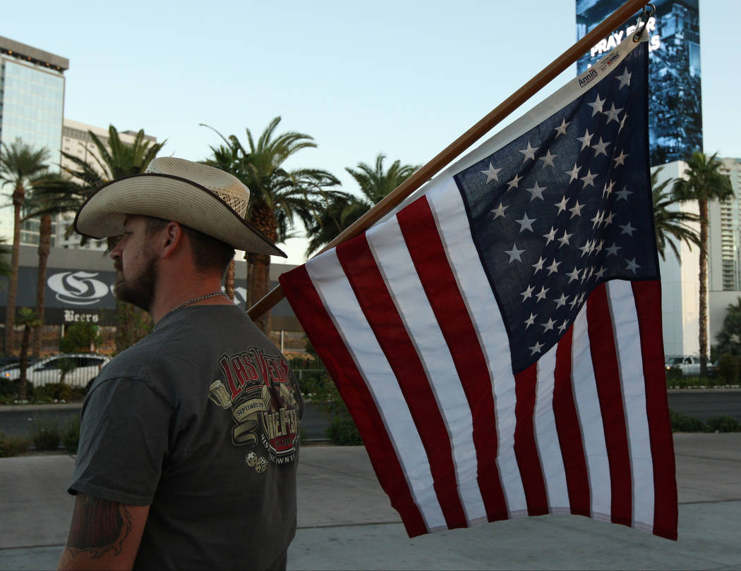 Las Vegas local Bryan Houghton holds the American flag while a crowd gathers for a candlelight vigil ceremony near East Sahara Avenue and South Las Vegas Boulevard that honors the victims of the s ...