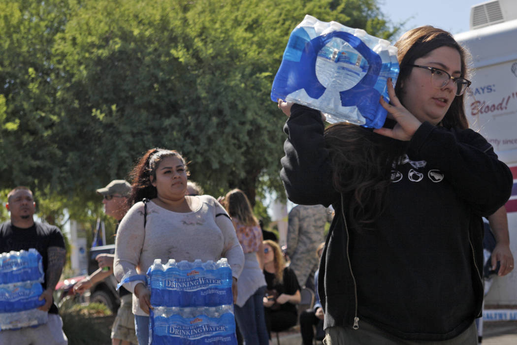 Taylor Cerrillo carries a pack of donated water to a 	University Medical Center parking lot in Las Vegas, Monday, Oct. 2, 2017. UMC set up a blood donation area to assist with victims injured in t ...