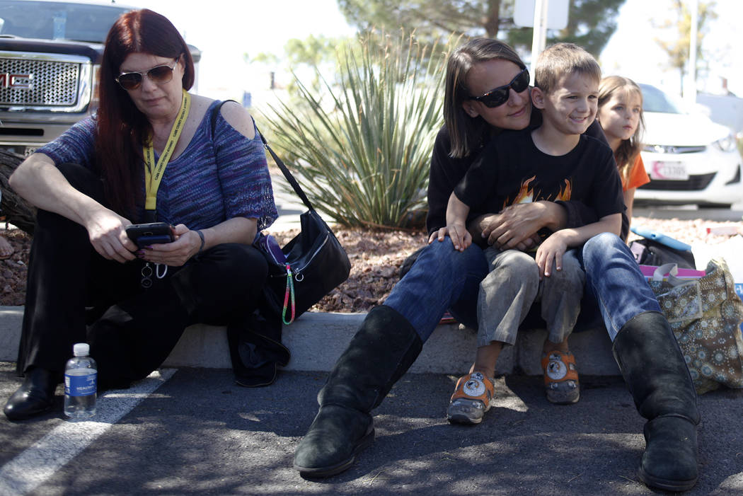 Kirsten Ashley, from left, Anina Duren, her son Wyatt duress, 5, and her daughter Kylie Duren, 7, behind her, wait to donate blood at the University Medical Center parking lot in Las Vegas, Monday ...