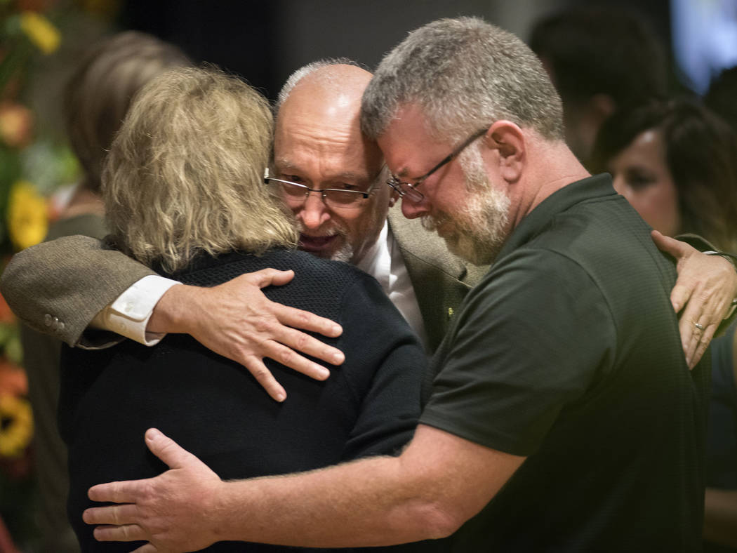 Sonny Melton's father, James Warren Melton, hugs friends Monday, Oct. 9, 2017, during Sonny's visitation at Big Sandy High School in Big Sandy, Tenn. Sonny was killed during a mass shooting at a c ...