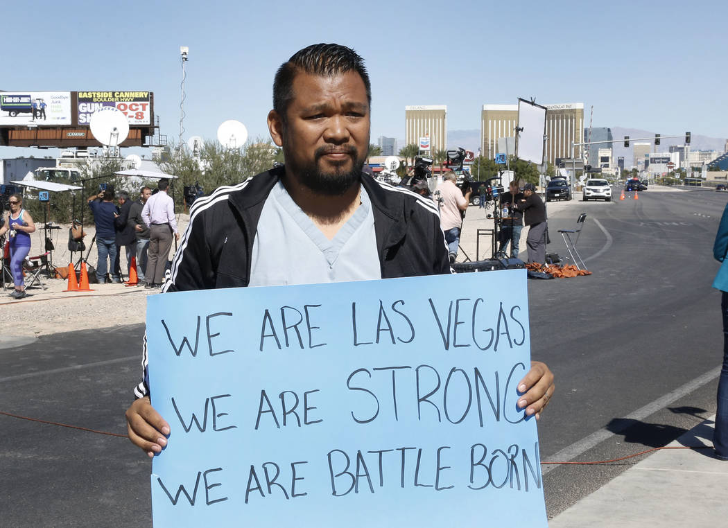 "Jon Dimaya, nurse at Sunrise Hospital, holds a sign that reads ""We are Las Vegas, We are Strong, We are Battle Born'' on Las Vegas Boulevard near Mandalay Bay hotel-casino on Monday, Oct. 2, 2017. ..."